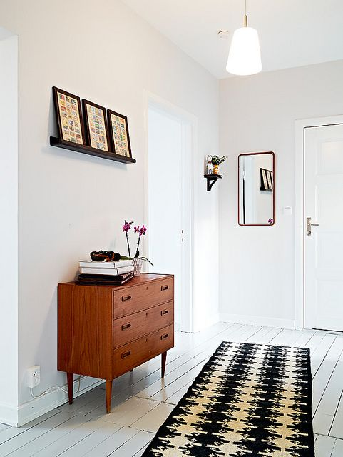 This is how medium-toned wood, and some black and white can ground a white-painted space while keeping it airy and bright. #white #foyer #midcentury