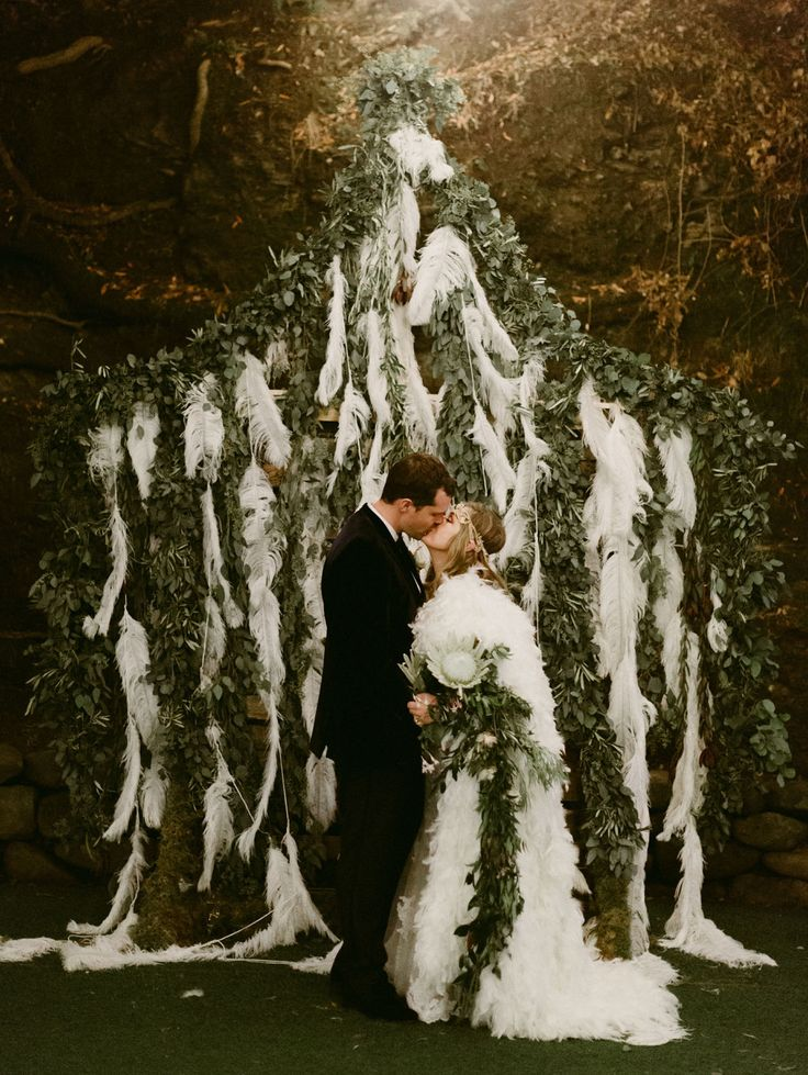 Boho Feather Cape Wedding // unique wedding backdrop of foliage and feathers