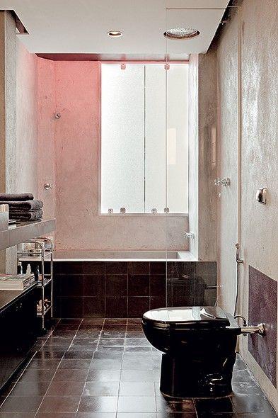 Em cima da banheira de alvenaria com cimento queimado, o teto é pintado de preto e tem lâmpada fluorescente vermelha com efeito de cromoterapia. O vaso sanitário e piso na cor preta deixam o ambiente masculino. Casa do designer de interiores Sandro Brasil