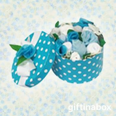 A beautiful posy of white and blue babywear for the new arrival. All presented in a classic hat box with blue wrapping and ribbon   1 vest 2 face cloths 1 leggings 1 beanie 1 pair of booties 1 bib Decorative flowers and butterflies