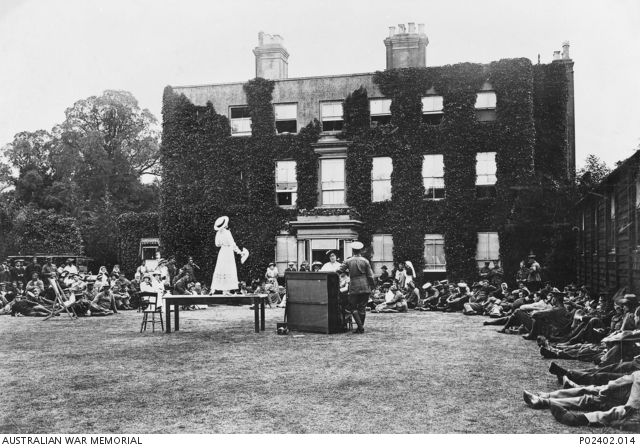 First concert party to be staged on the lawn of Harefield House when it was used as No. 1 Australian Auxiliary Hospital (1AAH). An entertainer, perhaps Miss Rita Fiske, is standing on a table ...