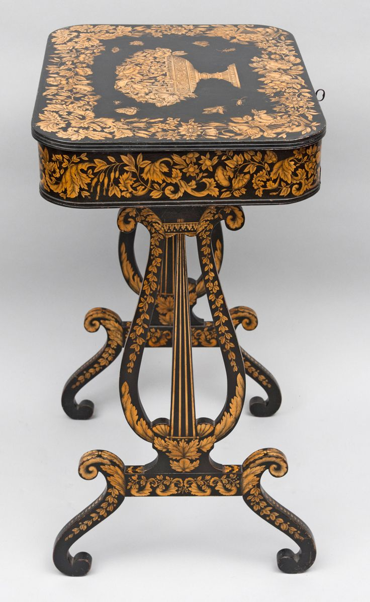 A Regency penwork sewing table. 1810. Penwork is a type of decoration applied to japanned furniture in the late 18th and early 19th centuries, mainly in England. Furniture to be treated in this way was first japanned black, then patterns were painted on in white japan and finally the details and shading were executed in black India ink with a fine quill pen. The effect is delicate and lacy, rather like an etching in reverse, with white motifs on a black ground (Penguin Dctnry of Decorative…