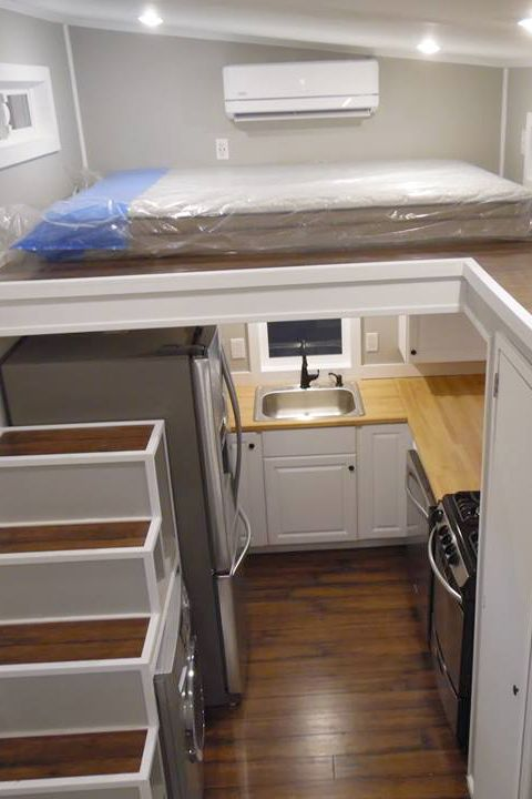 Inside is a full kitchen with a French door refrigerator, dishwasher, freestanding propane range, butcher block countertops, washer/dryer combo, and upper cabinets.