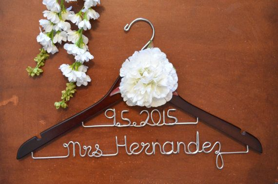 Order a personalized wedding dress hanger for the beautiful bride on her special day! Give her a gift at her bridal shower that will add a unique touch to her wedding gown every time she looks at it for years to come! Custom hangers are great for thank you gifts for your bridesmaids and the rest of the bridal party. They make a great photo op and a memory they can use forever! Customize the wood hanger color, wire color and add a flower or bow in their favorite colors or in the wedding theme…