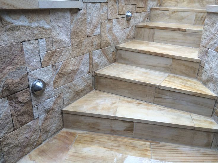 Sandstone stairs, cladded walls and stainless steel lights.