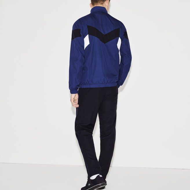 Lacoste Sport Tennis brings its signature to this tough tracksuit with a V-shaped colorblock, subtle piping, shiny taffeta and elasticized finishes.