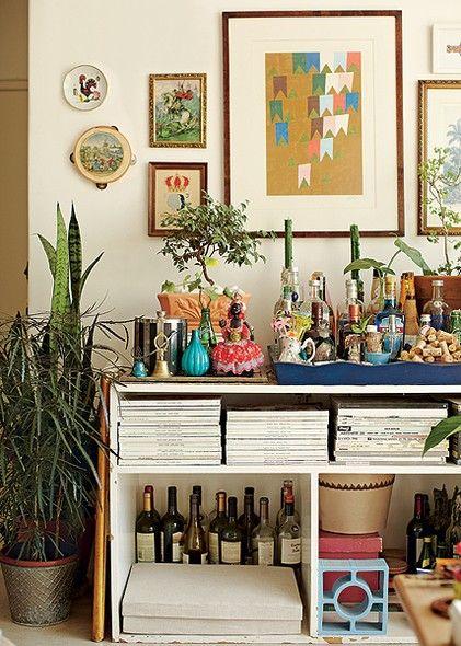 O nicho de um antigo guarda-roupa agora acomoda o bar e revistas, na casa do diretor de arte de cinema Thiago Bastos. A decoração mistura garrafas cheias e vazias a plantas, obras de arte e pratos na parede