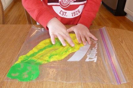 "Children explore colors they can make with paint that is placed in reclosable plastic bags (""squish bags"")."