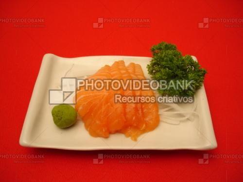 Sashimi | PHOTOVIDEOBANK Imagem de sashimi de salmão fatias com nabo em tirinhas, salsa tonkatsu e wasabi prato culinária comida japonesa fundo vermelho para sushi