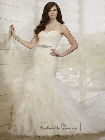 This whimsical fit and flare wedding dress features a bodice with soft lace under tulle, a sweetheart neckline, and a skirt that blooms with tiered layers down to a court train. Crystal beaded sash accentuates the waist.