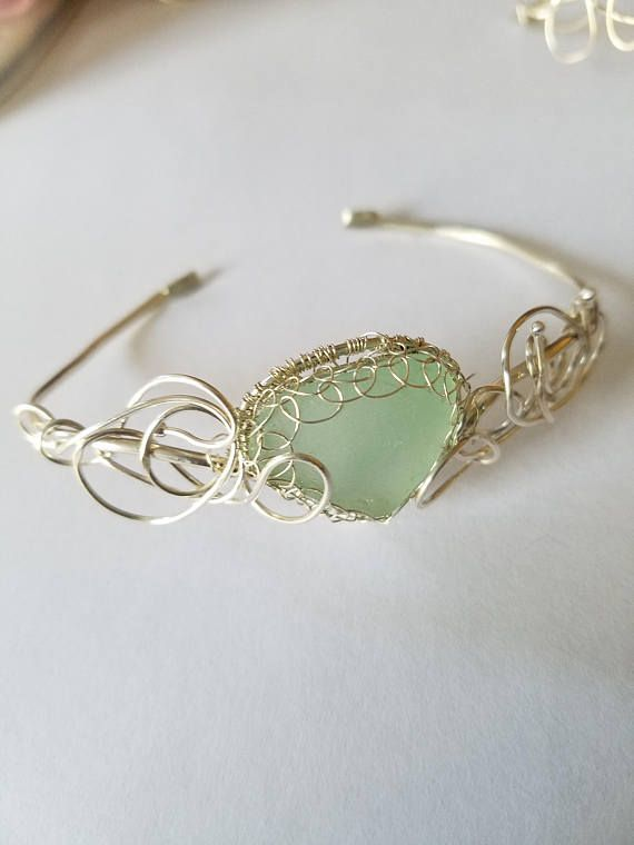 Here we have an lovely sea glass bracelet. It is adjustable to fit up to 7.5 inches. It is easily molded to your forearm to sit where you like it. Each bracelet is individually hand made. This one has sea foam sea glass from Puerto Rico.