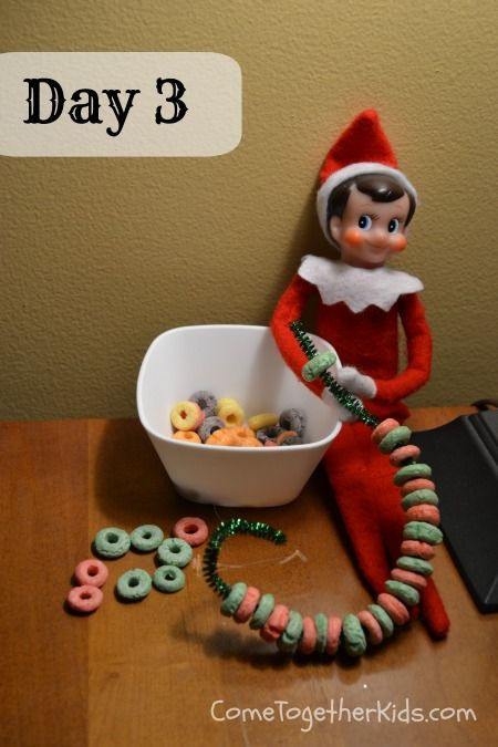 Elf On The Shelf making a Christmas tree garland with Fruit Loops.