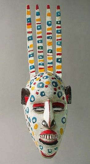 N'tomo Mask. Bamana people, Mali. Painted wood. Characterized by multiple horns and, sometimes, eyelashes and white shell ornamentation, these masks serve to protect young boys during their first initiation cycle before circumcision. This style, with the head of the woman in front of the horns is made by Bougouni people in Mali. The number of horns make reference to specific characteristics of males (3 or s3 horns) or females (4 or 8 horns) and the androgynous (2, 5 or 7).
