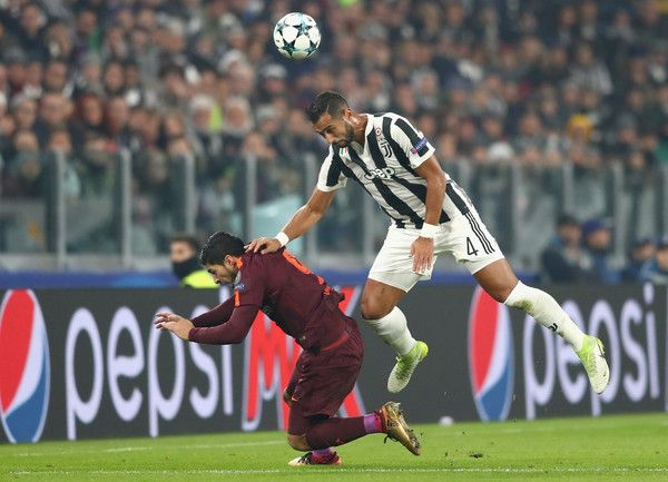 Medhi Benatia of Juventus and Luis Suarez of Barcelona battle for possession in the air during the UEFA Champions League group D match between Juventus and FC Barcelona at Allianz Stadium on November 22, 2017 in Turin, Italy.