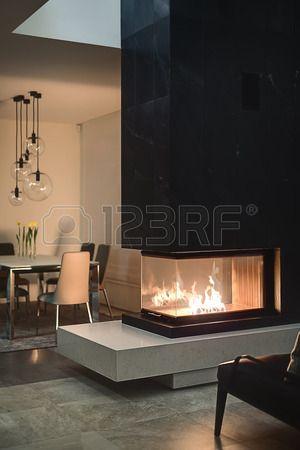 chimenea de cristal con el fuego ardiente dentro de una chimenea y negro. En el fondo hay una mesa con flores en jarrones, sillas y lámparas redondas de cristal sobre ellos. Las paredes son de color. En el piso hay azulejos y una alfombra. En frente de la chimenea hay un da