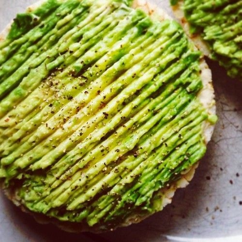 Hummus and mashed avocado spread on a brown rice cake with pepper