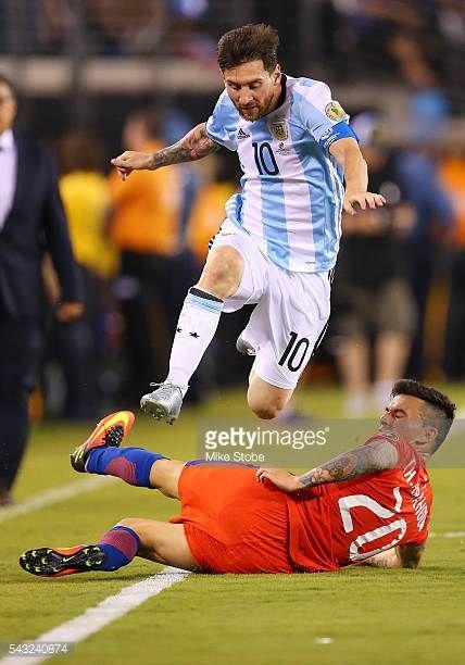 Lionel Messi of Argentina leaps over Charles Aranguiz of Chile during the Copa America Centenario Championship match at MetLife Stadium on June 26...