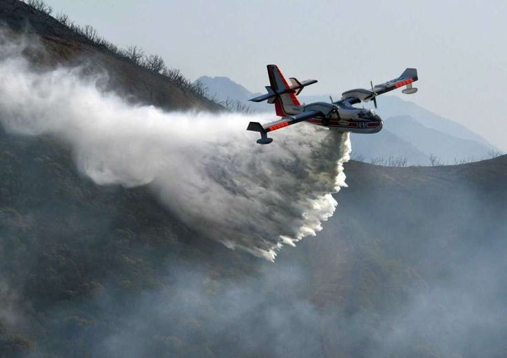 In this photo provided by the Santa Barbara County Fire Department, a Bombardier 415 Super Scooper makes a water drop on hot spots along the hillside east of Gibraltar Road in Santa Barbara, Calif., Sunday morning, Dec. 17, 2017. One of the largest wildfires in California history is now 40 percent contained but flames still threaten coastal communities as dry, gusty winds are predicted to continue. (Mike Eliason/Santa Barbara County Fire Department via AP) Photo: Mike Eliason, AP / Santa…