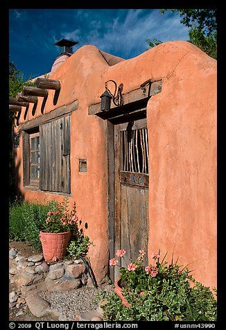 Flowers, adobe wall, and weathered door. Santa Fe, New Mexico, USA