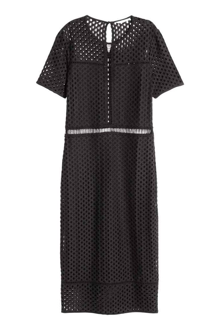 Kanten jurk: Een lange, getailleerde jurk van elastisch kant met een ajourdessin. De jurk heeft korte mouwen en een splitje met een knoop in de nek. Deels gevoerd met tricot.