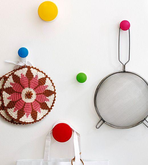 Päť nástenných úchytiek IKEA v žiarivých farbách, na ktorých sú zavesené rôzne kuchynské pomôcky.