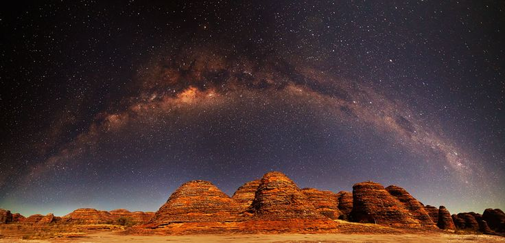 Milky Way Over the Bungle Bungles   Image Credit & Copyright: Mike Salway Which part of this picture do you find more interesting -- the land or the sky? Fortunately, you don't have to decide and can enjoy both together in this beautiful 8-frame panorama taken from the dark skies of Purnululu National Park about two months ago. [domes appear as huge layered beehives] [The photogenic Milky Way band formed over 10 billion years ago and now includes many well-known nebulae and bright stars]