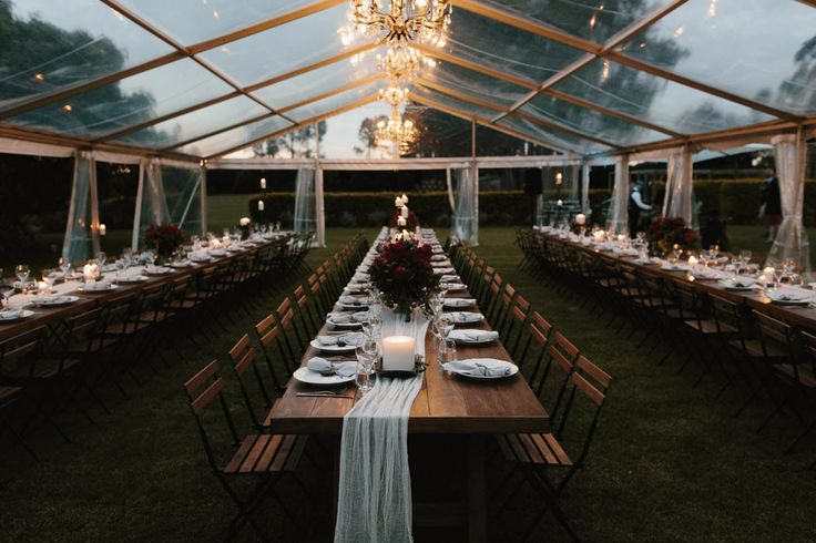 Transparent tent, chandeliers, and gauzy table runners | Image by Jimmy Raper Photography
