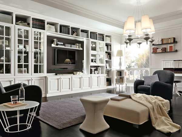 spazio living con scaffalatura bianca, vetrine e spazio tv, poltrone nere, puof e lampadario con paralumi