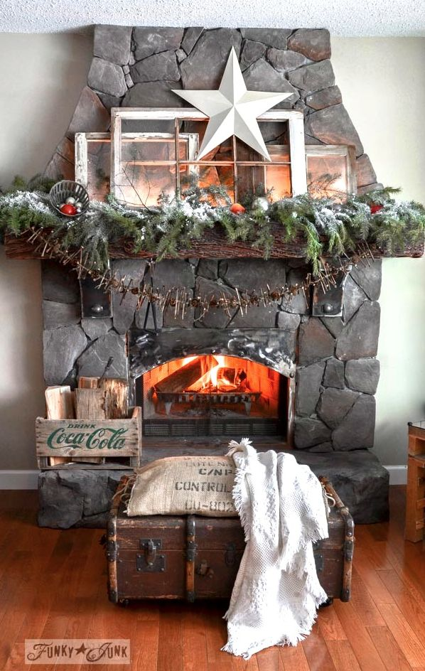 Old windows Christmas fireplace mantel / Funky Junk Interiors  Doesn't this old window mantel resemble a snowy cabin in the woods, flickering with the warmth of a fireplace? Realistic indoor snow tips in this one too!