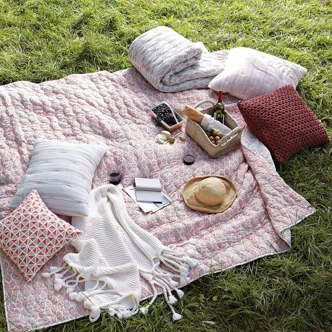 Picnic. Blankets and cushions for comfort.  Food and book for enjoyment.
