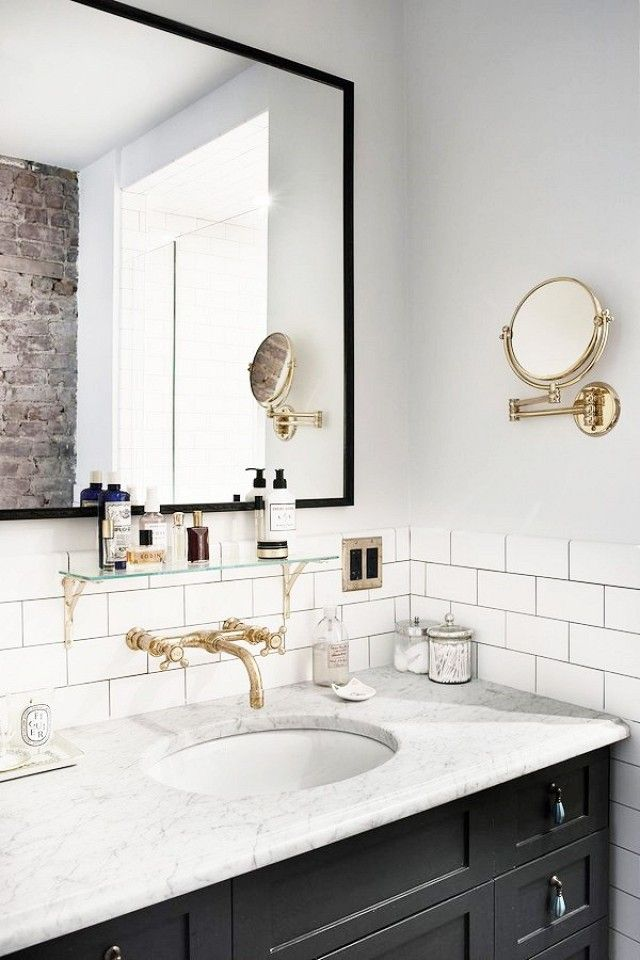 Beautiful black and white bathroom with brass sink faucet, white subway tiles, and painted recessed panel cabinets.