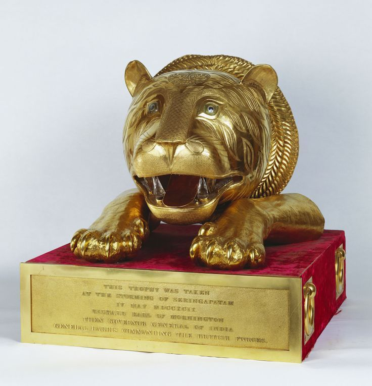 Gold tiger's head, Indian, 1799. Gold, rubies, diamonds, rock crystal,  Royal Collection © Her Majesty Queen Elizabeth II  Provenance: Presented to William IV by the East India Company, 1831  William IV, King of the United Kingdom (1765-1837)  Tipu Sultan (1750-99) succeeded his father, Haidar Ali, as ruler of the South Indian state of Mysore in 1782, building a sophisticated and modern court around his palace at Seringapatam. For much of his reign he was engaged in hostilities against the…