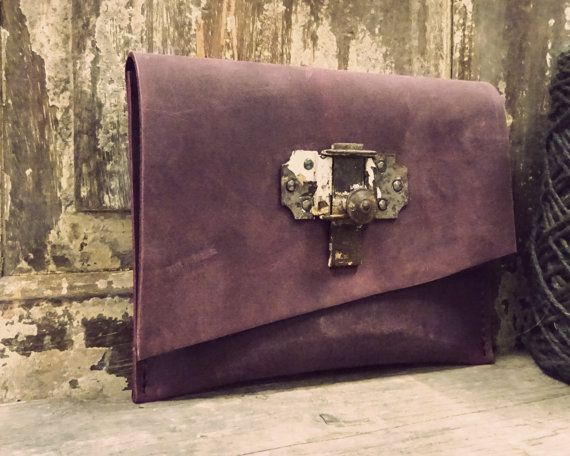 A handmade leather clutch with antique lock to shop.