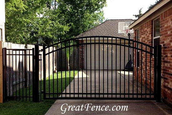 Black smooth top, single swing driveway gate with sunburst arch.
