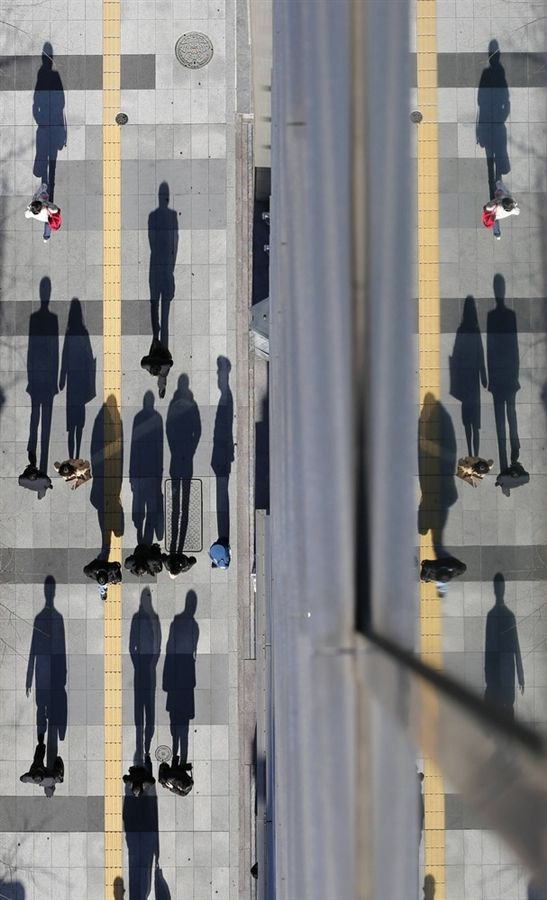 Pedestrians cast shadows on a sidewalk near the headquarters of the Bank of Japan in Tokyo, Japan by Kim Kyung-Hoon Reuters . Photos of the Day: 20121220