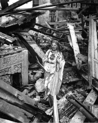 Still standing in the rubble of a church in the war-blasted town of Dulag, a statue of the sacred heart appears to gaze in quiet sorrow on the destruction wrought by battle's fury seething over Leyte Island, Philippines, 1944.