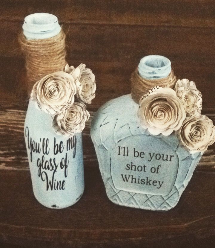 Distressed Wine and Whiskey bottle set. Hand rolled paper flowers from book pages wrapped in twine. Shabby Chic! #LittleMotherHubbardCrafts