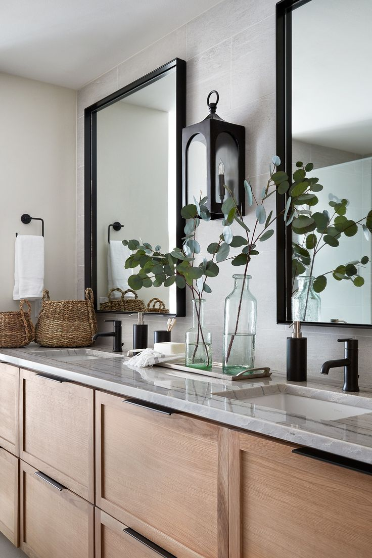 The cool grey tones on the countertops and tiles, paired with the same warm wooden cabinetry we used in the kitchen, played into the spa feeling in this space. Plus black metal hardware, mirrors and light fixtures bring in the modern details from the rest of the house.