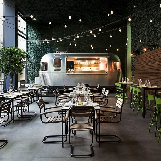 This is an urban garden after all; steel and glass are also used indoors, notably in the shiny Airstream trailer kitchen parked up inside and the double height doors that open wide to let the garden atmosphere flood in...