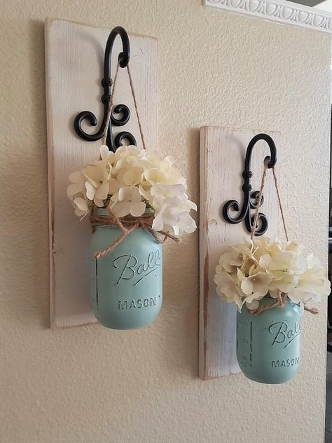 These rustic country style mason jar sconces are the perfect touch to your home decor. They bring warmth and beauty to any room. This listing is for 2 Sconces so for each quantity of one at checkout you are ordering one set of 2. Scroll through the listing to see your sconce finish/flower/jar paint color options. The Sconce pictured is done in Antique White the Jars are done in Sea-foam Blue. (Flowers are optional) {Please Leave Me a Note At Checkout With Jar Color…You Can See Y…