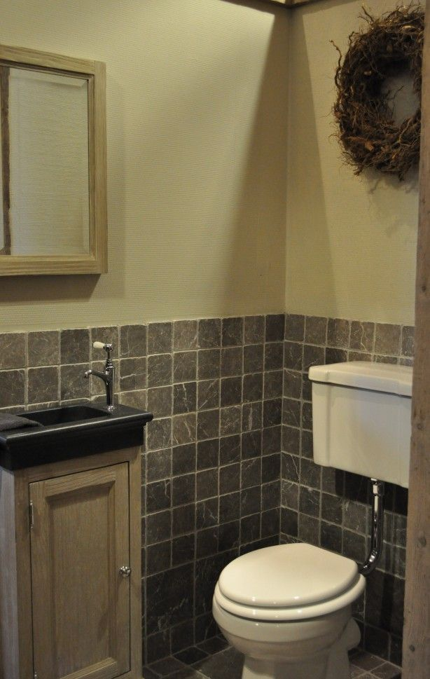 Landelijke toilet met Shadow natuursteen wand en vloer. Toilet meubel woodwashed met graniet wasbakje. Toilet met laaghangend reservoir. Van Heck experience store showroom foto