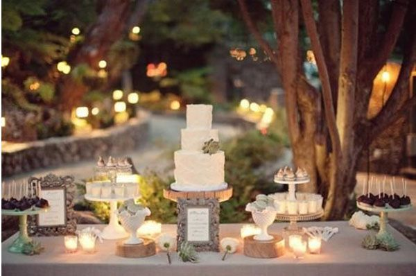 Outdoore wedding dessert table with wedding cake centrepiece on wooden tree slices and beautiful candle light. Wedding Dessert Table Inspiration #wedding