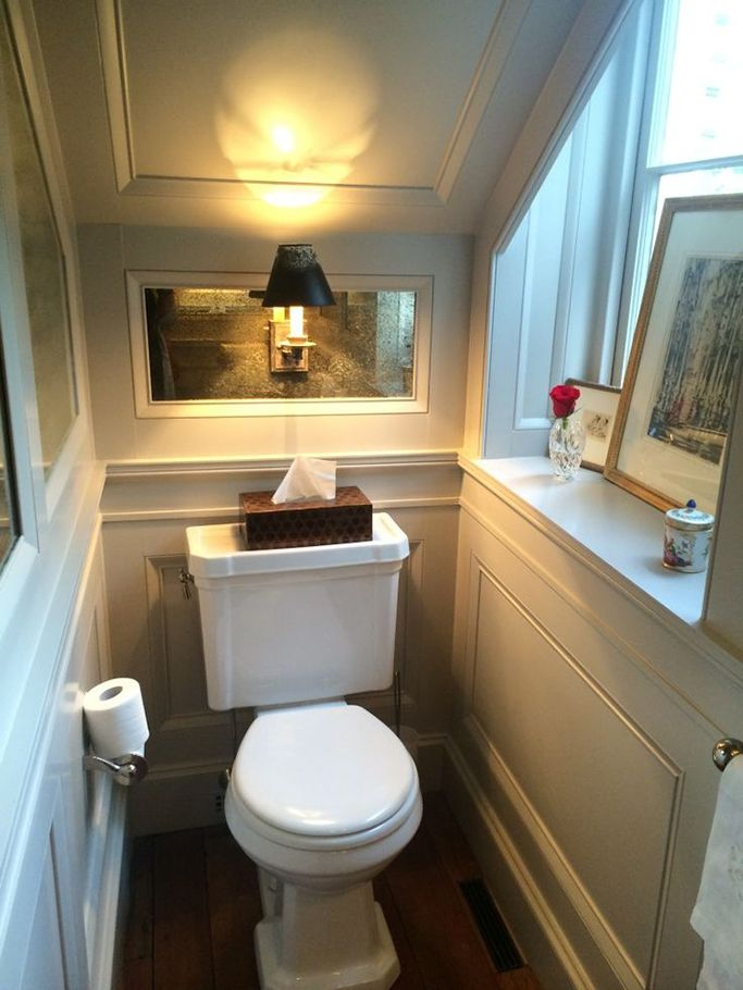 Classically designed under stairs toilet with window.