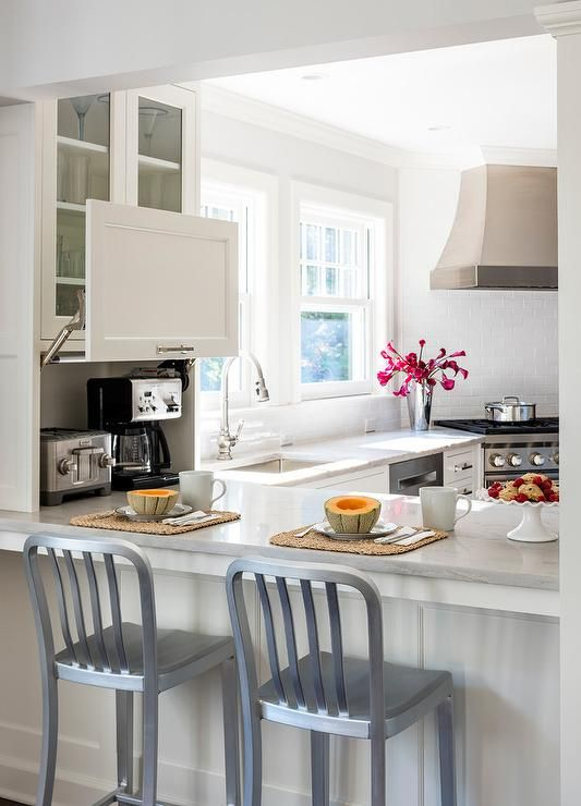 Two 1006 Navy Counter Stools sit at a white peninsula topped with a White Macauba Quartz countertop and ending glass front cabinets fixed above a coffee maker hidden behind a white garage cabinet.