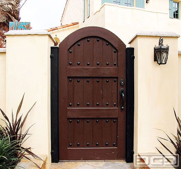 Built on a steel frame and fortified with steel jambs this gate will not only adds architectural value to the home but also durability that will last. Designed with a prominent arch and enhanced with oversized decorative iron clavos this custom gate is a gem!