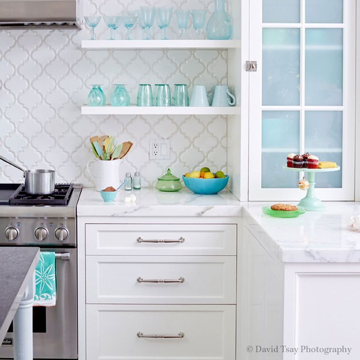 chic white kitchen features white cabinets paired with white marble countertops and a white arabesque tiled backsplash mission stone tile beveled arabesque