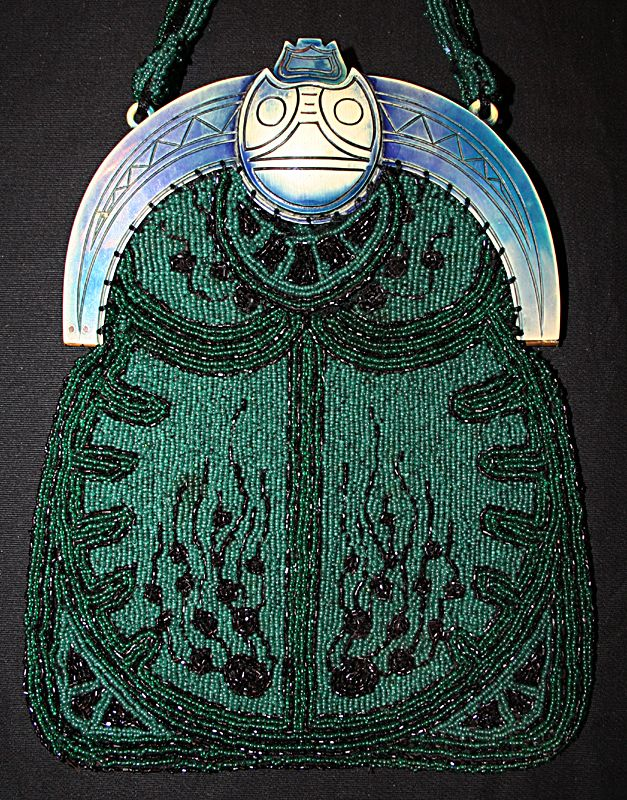 I love this extraordinary beaded bag. Here the celluloid frame is simplistic and other than a clever clasp (you push the top portion of the scarab's head back to open) there's not much detail. But the beaded bag, whose design mimics a scarab's body, is so wonderful that it elevates this to a great purse.