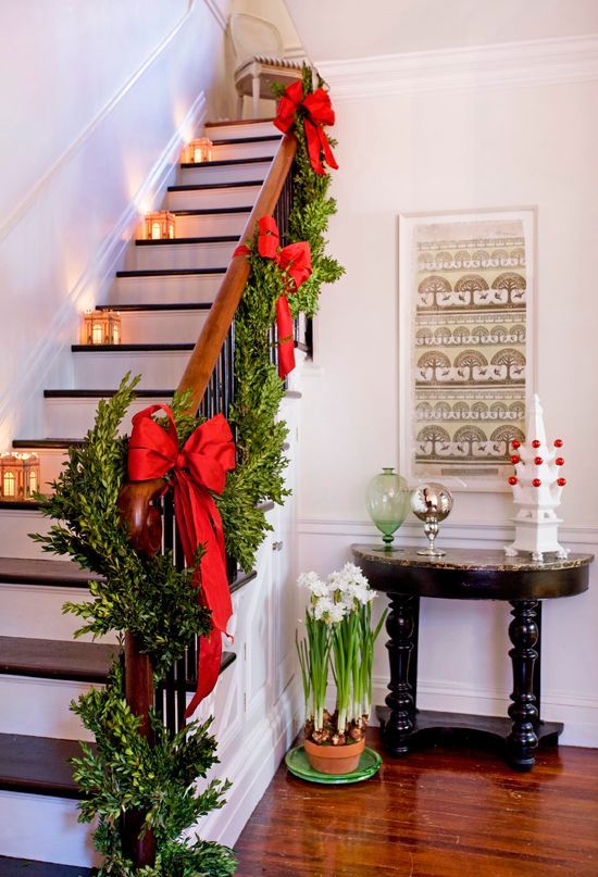 Architectural paper lanterns and lush greens encircling the banister add traditional charm to this staircase. ~ 50 Stunning Christmas Staircase Decorating Ideas - Style Estate -