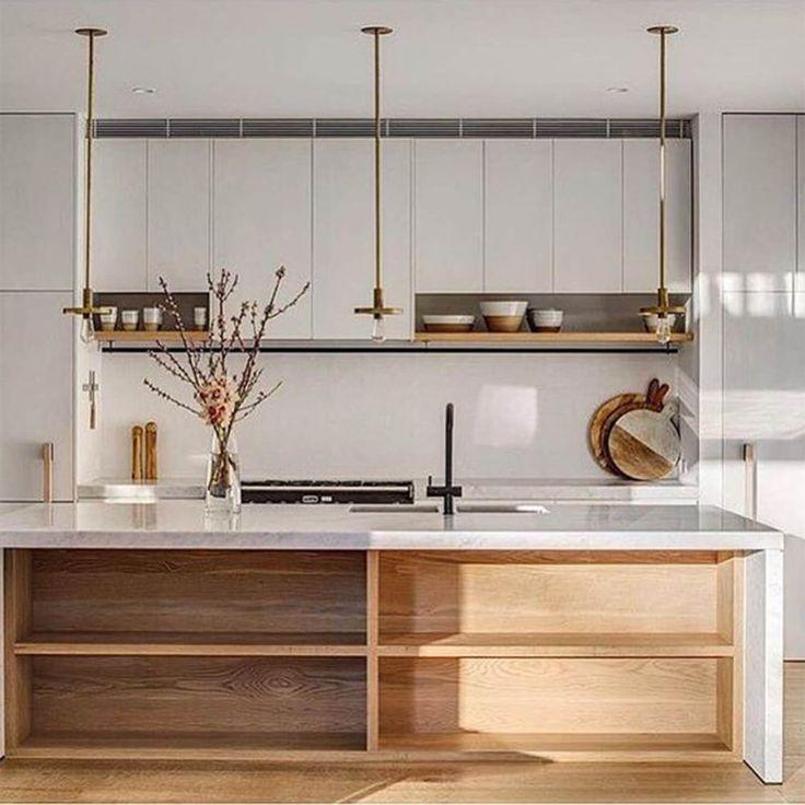 Madeira e elementos em latão garantem toques de cor e calor nesta cozinha minimalista, um projeto do escritório Alwill Interiors! Achamos uma ótima ideia as prateleiras decorativas junto aos armários!