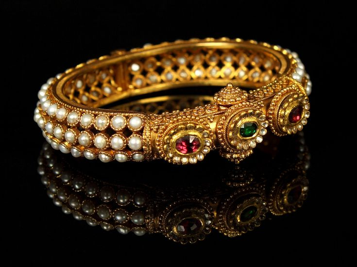 Kundan Gold Kada. Regal in appearance, traditional in craftsmanship, this Kundan kada reflects the mystique and magic of a bygone era from the pages of history. This wide, antique finish gold kada is encrusted with rows of luminous pearls. The eye-catching head of the kada is embellished with the glimmer of neon pink Tourmalines, green gemstones and sparkling Kundan. The side screw ensures safety, comfort and the perfect fit,